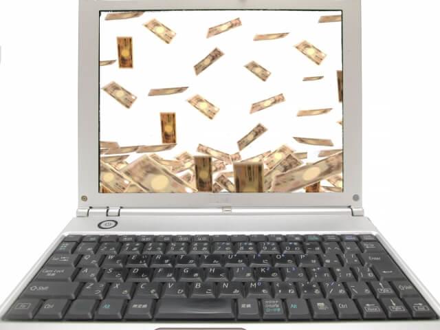 ノートパソコンの画面に万札が舞っている画像