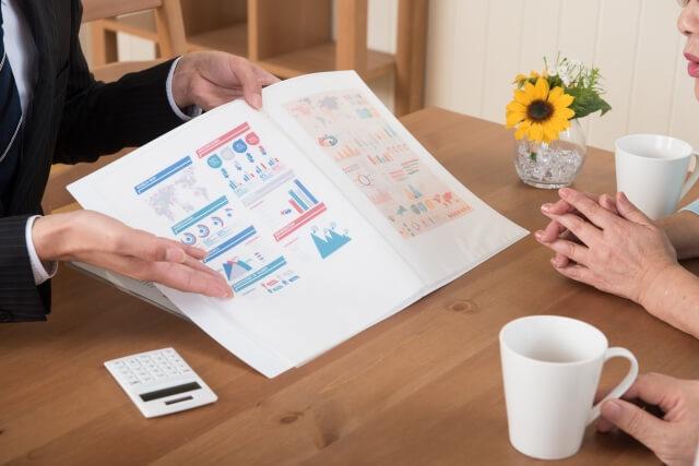 営業マンがパンフレットを紹介している画像
